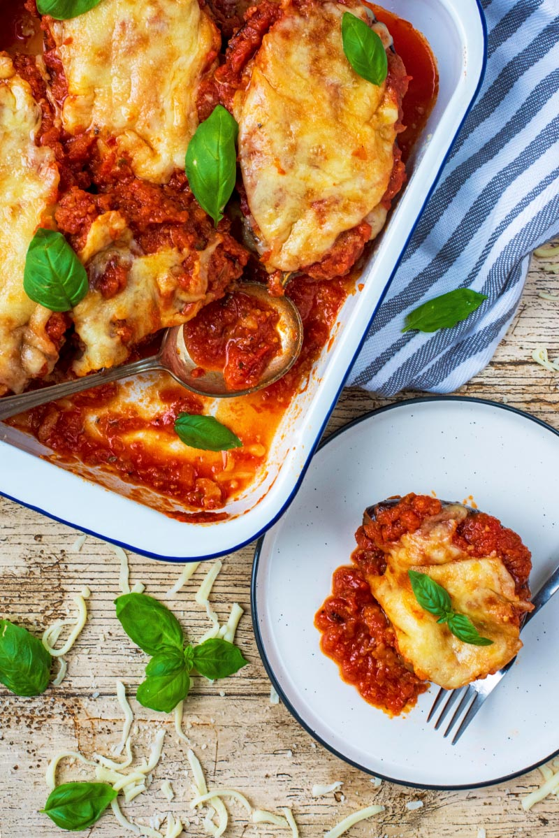 A baking tray of eggplant parmesan with more on a plate next to it