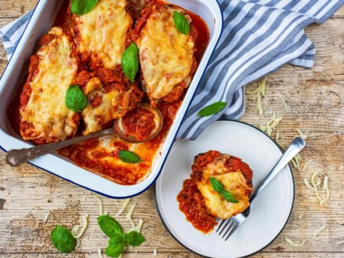 A plate of Healthy Eggplant Parmesan next to a baking tray with more of it in