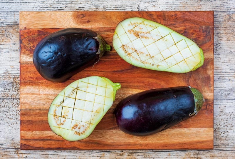 Two eggplants sliced in half and scored diagonally
