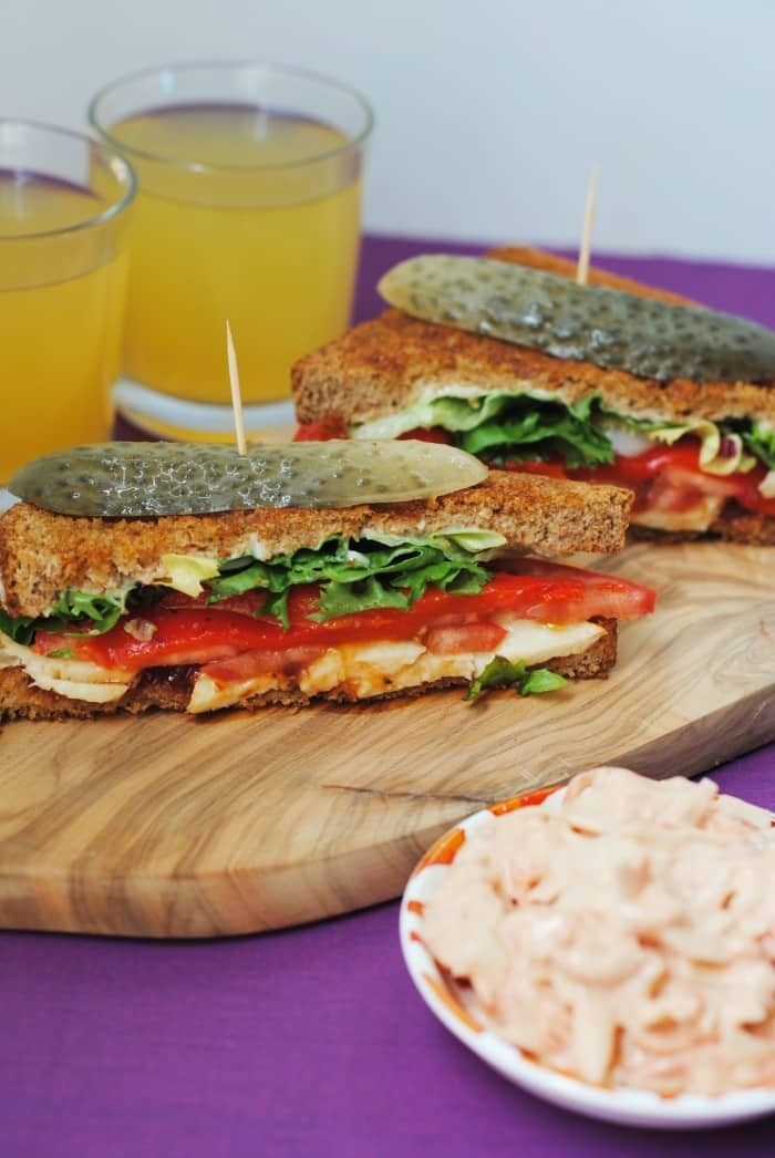 Two toasted sandwiches on a serving board with a small bowl of coleslaw in the foreground