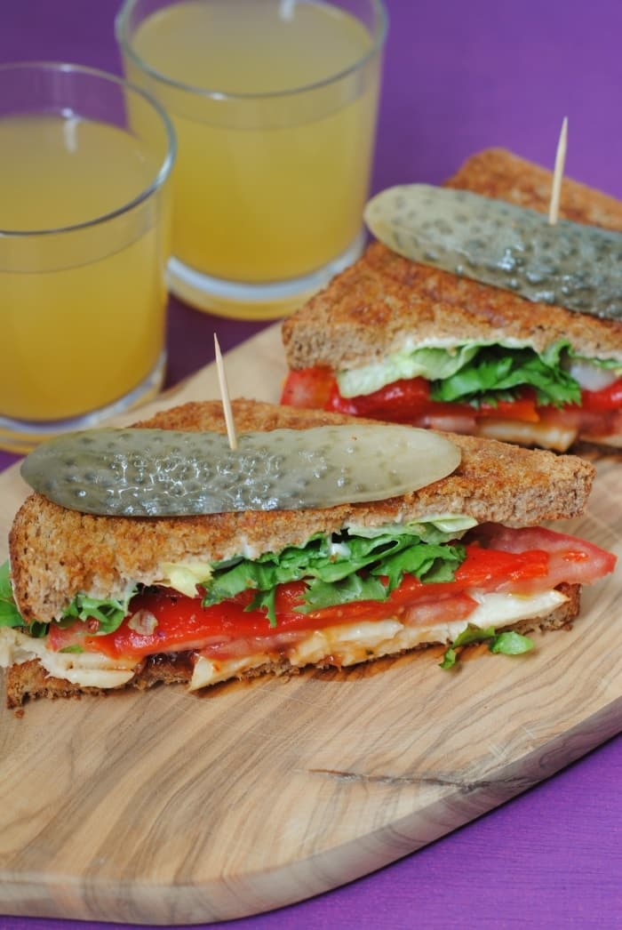 Two halloumi and red pepper sandwiches on a wooden board in front of two glasses of orange juice