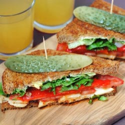 Two halloumi and red pepper sandwiches on a wooden board with sliced pickles on top