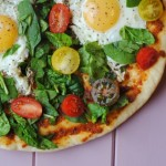 Breakfast Flatbread topped with eggs, tomatoes and spinach
