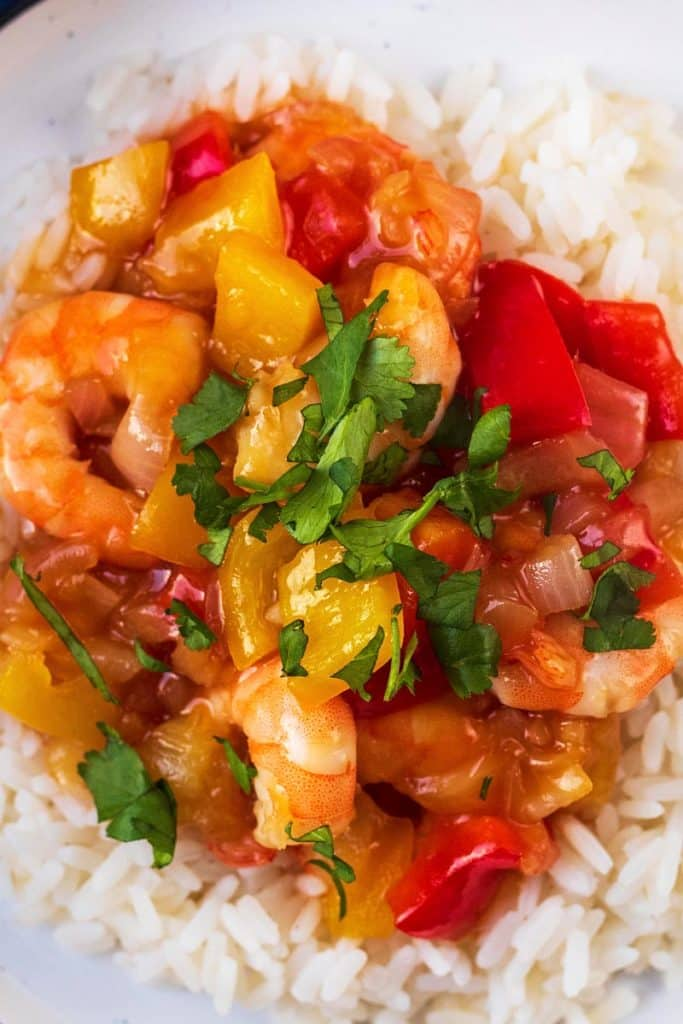Sweet and sour shrimp topped with cilantro leaves on a bed of rice