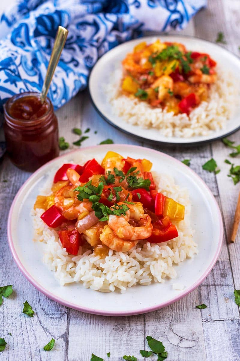 Prawns (shrimp) in a sauce on top of rice next to a small jar of sauce