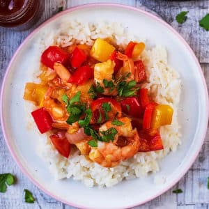 A plate of sweet and sour prawns on a bed of white rice