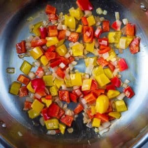 A large silver pan with chopped onion and red and yellow peppers cooking in it