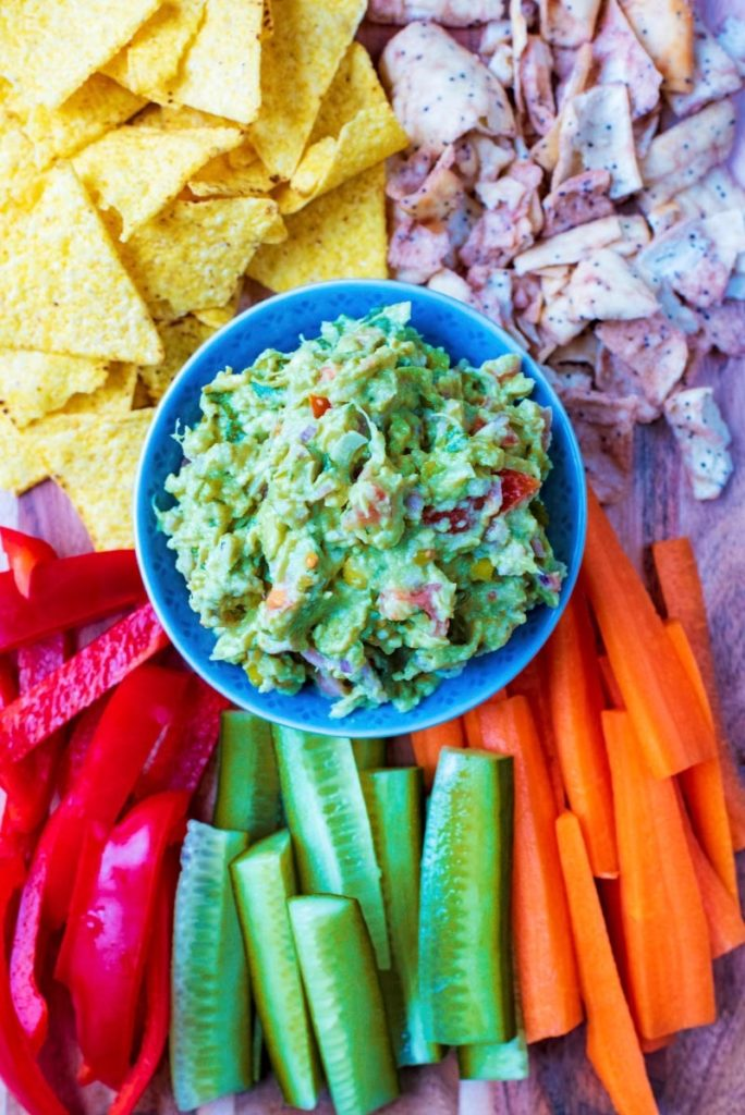 The best guacamole surrounded by sliced cucumber, carrot and pepper and tortilla chips