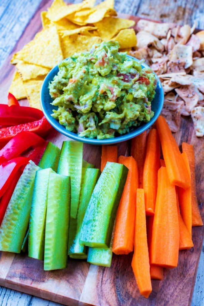 A bowl of guacamole on a serving board with crudités