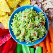 The best guacamole surrounded by sliced vegetables and tortilla chips