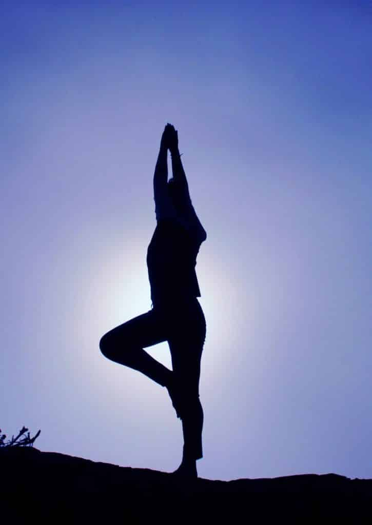 A silhouette of a person doing Yoga
