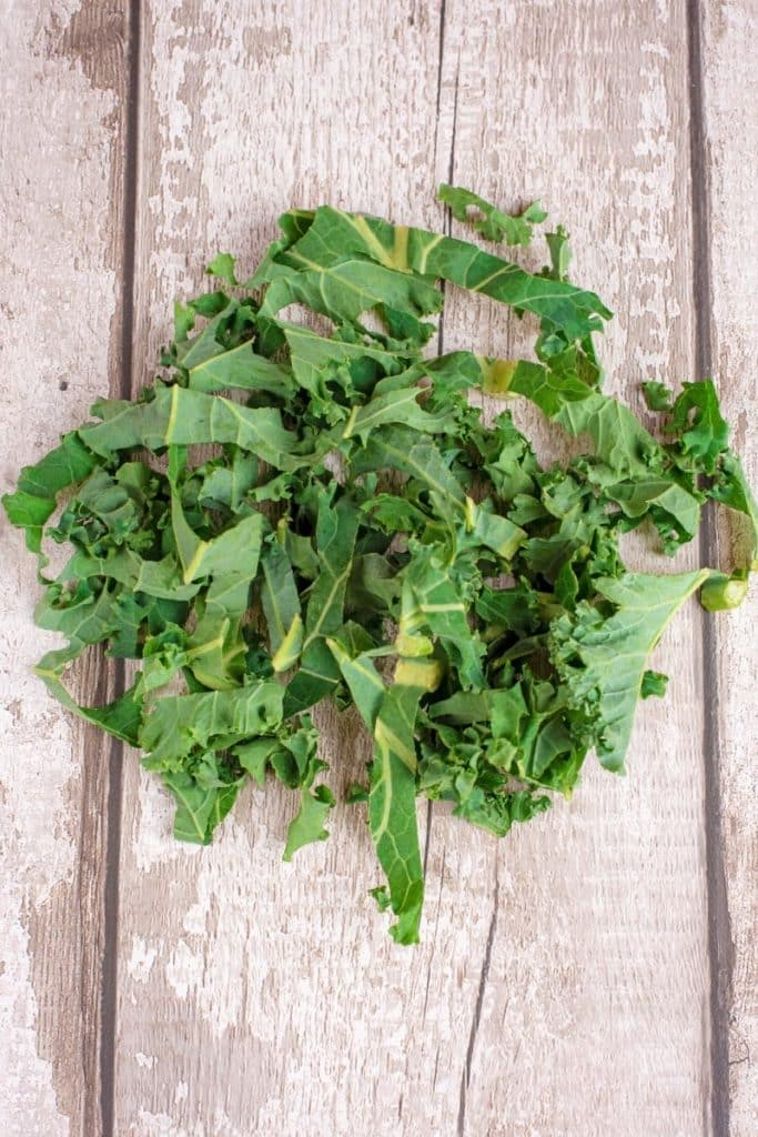 A pile of curly kale on a wooden board
