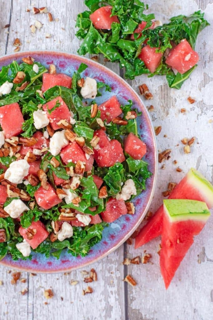 A salad made up of kale, watermelon and feta cheese on a blue plate