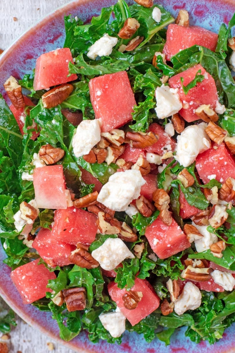 Cubes of watermelon, crumbled feta and chopped pecans on a bed of kale leaves