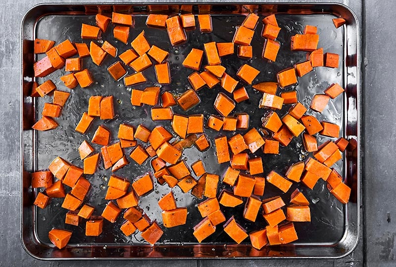 A large baking tray covered with cubes of sweet potato