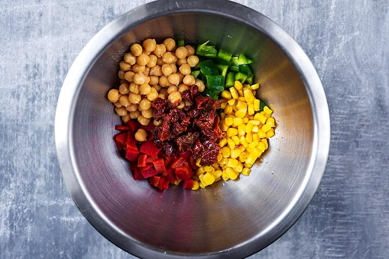 A mixing bowl containing chickpeas, chopped peppers, sun dried tomatoes and sweetcorn