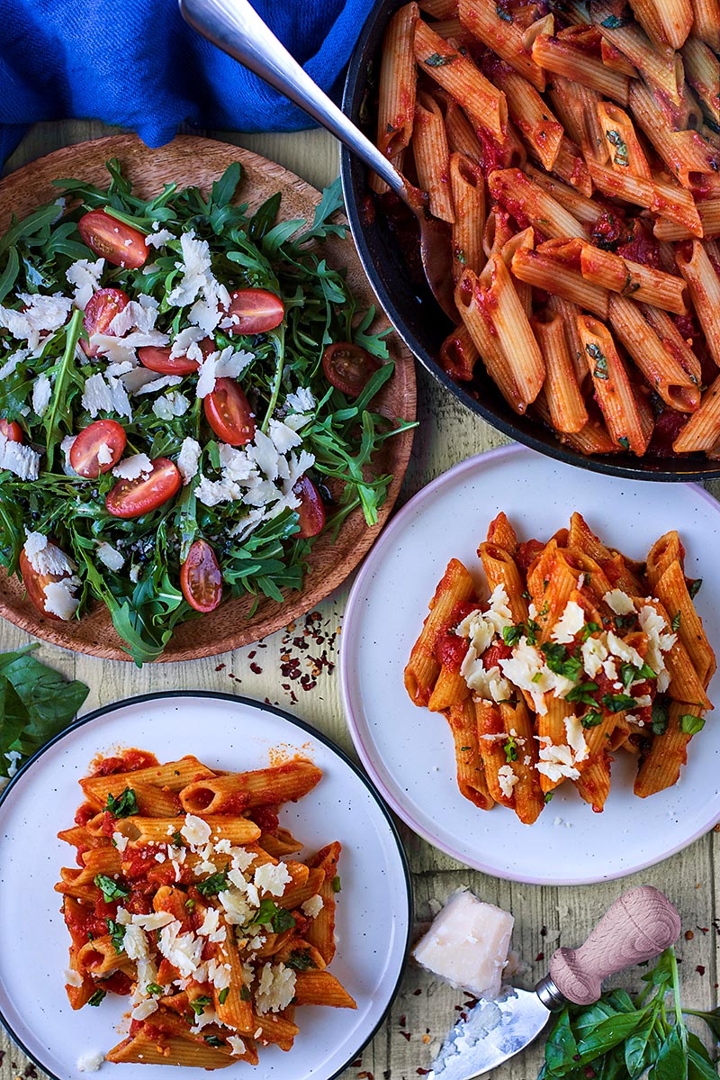 Two plates of penne arrabbiata next to a pan of more pasta and a plate of salad