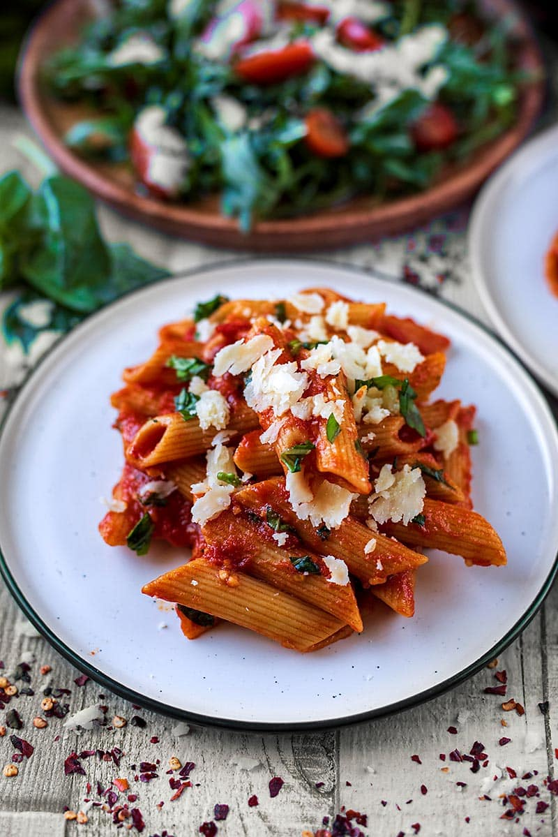 Tomato pasta on a plate in front of a plate of salad