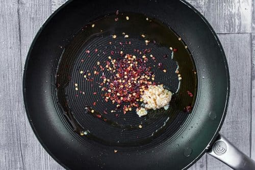 A frying pan with minced garlic and chili flakes cooking in it