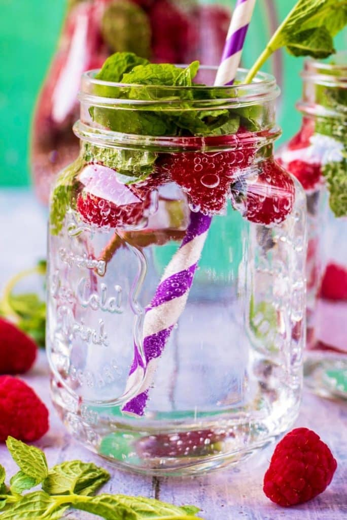 A mason jar filled with raspberry sparkling water with a striped straw