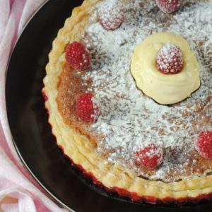 Bakewell Pudding on a black plate with a pink towel