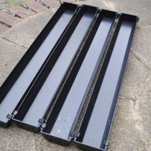 Four 1m lengths of black guttering with stop ends at each end and holes drilled in the gutter