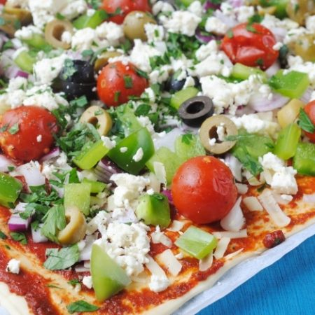 A Greek Pizza topped with olives, tomatoes and feta