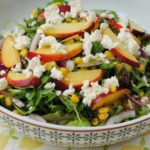Grilled peach salad in a patterned bowl