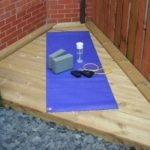 Yoga mat, yoga blocks, water bottle and resistance bands on a small wooden decking area