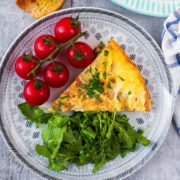 A slice of Spanish omelette on a plate with vine tomatoes and green salad leaves