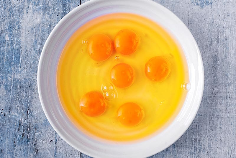 A large bowl with six eggs cracked into it