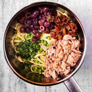 Cooked spaghetti in a pan with tuna, olives, tomatoes, peas and herbs