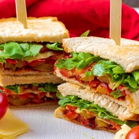 Two stacked Vegetable Pizza sandwiches with skewers through them