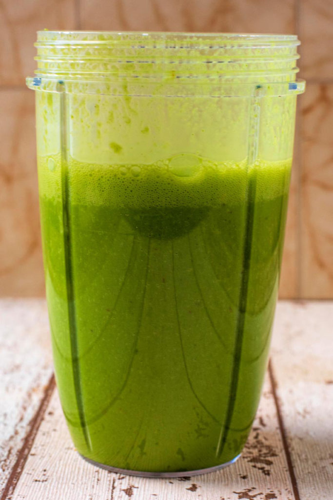 A blended green smoothie in a blender jug