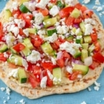 Greek Hummus Flatbreads sat on a blue cloth with chopped salad