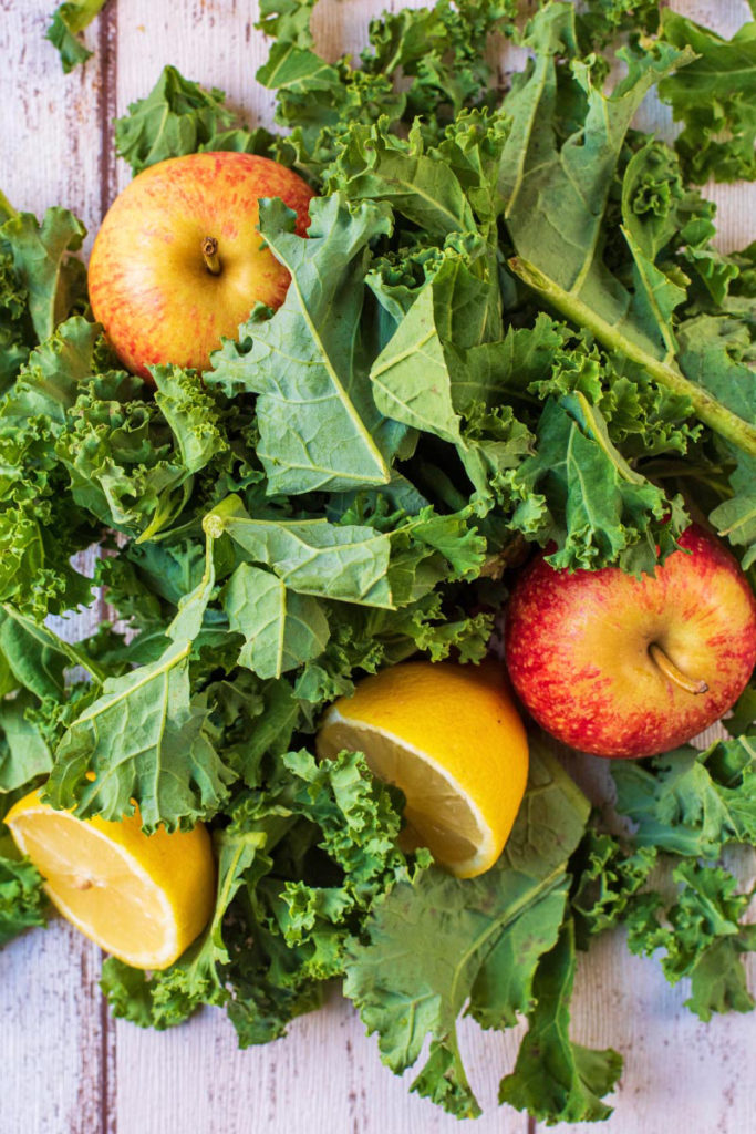A large pile of raw kale leaves, two apples and two lemon halves all on a wooden surface