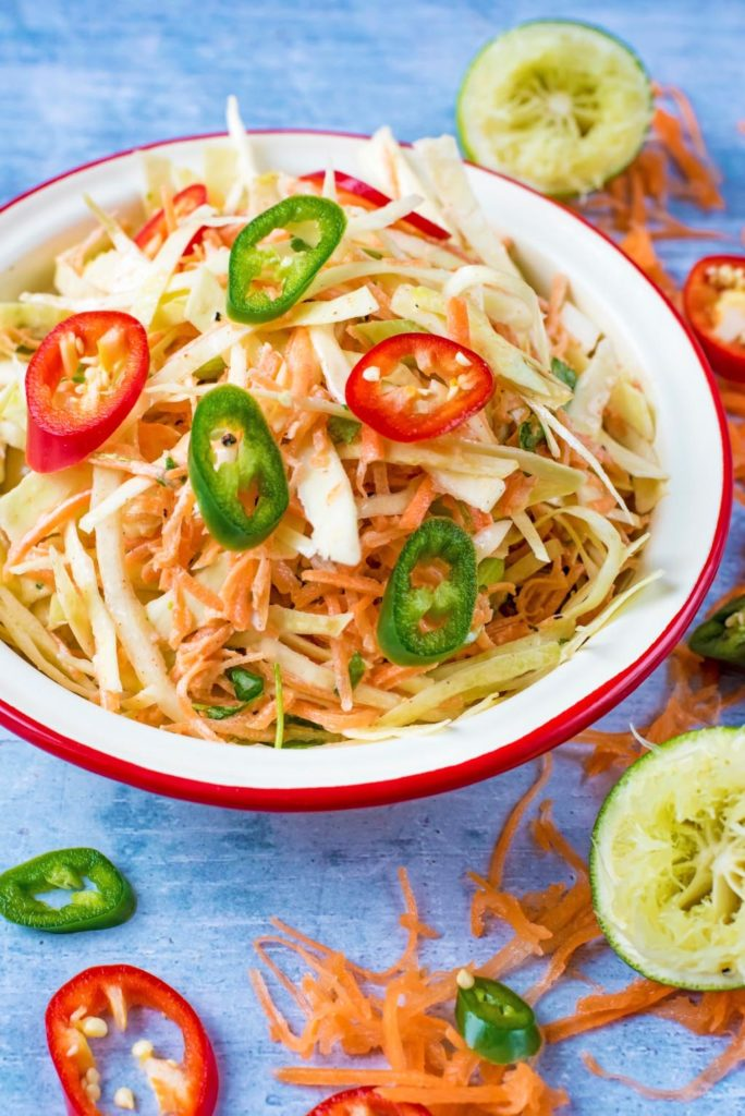 A bowl of coleslaw topped with sliced chillies