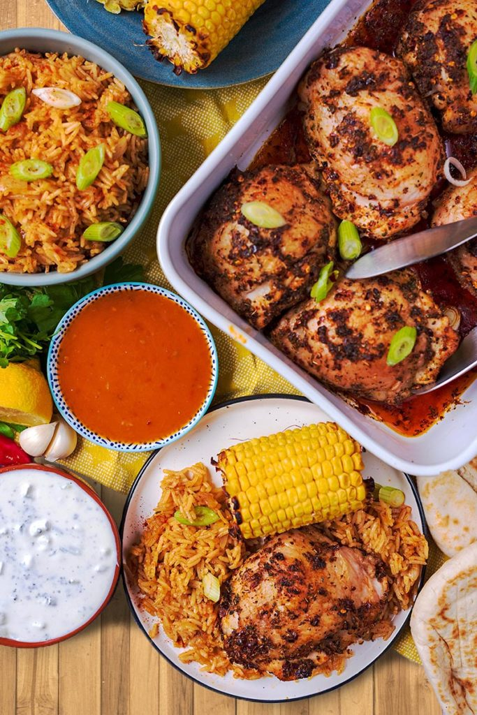 Peri Peri Chicken in a baking dish and on a plate with corn, rice, sauces and bread