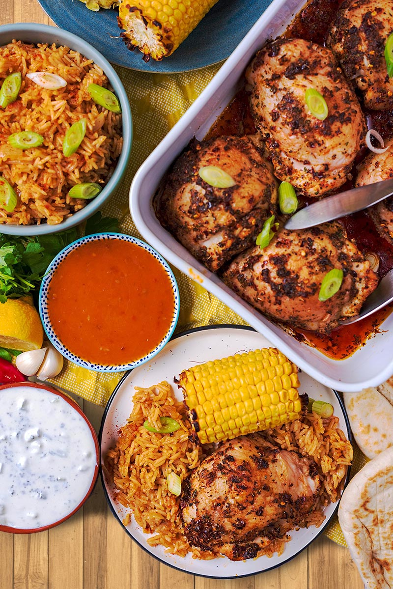 Peri Peri Chicken in a baking dish and on a plate with corn, rice, sauces and bread.