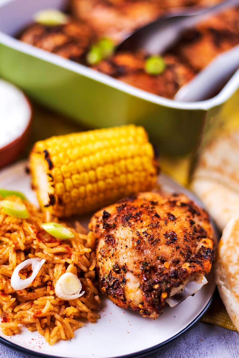 A chicken thigh, corn cob and rice on a plate in front of a baking dish full of chicken.