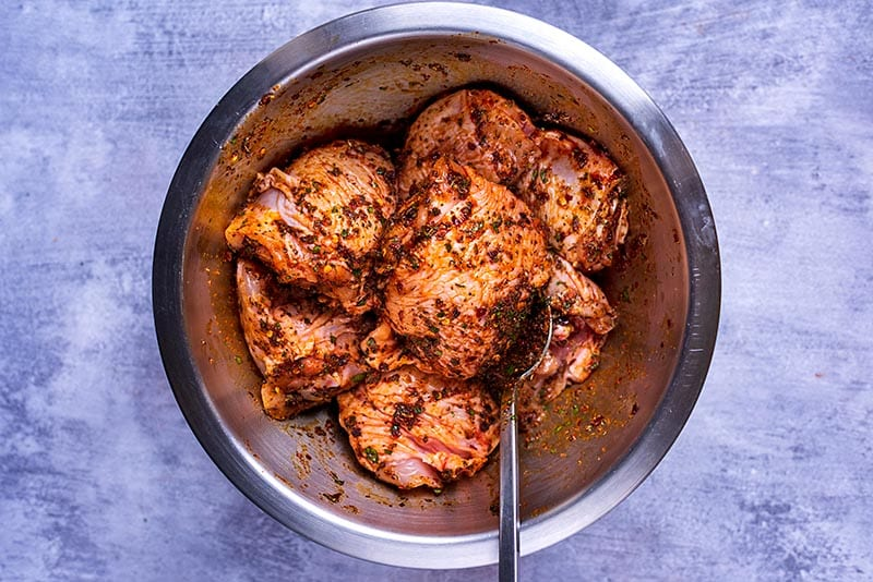 A bowl of chicken thighs coated in a marinade