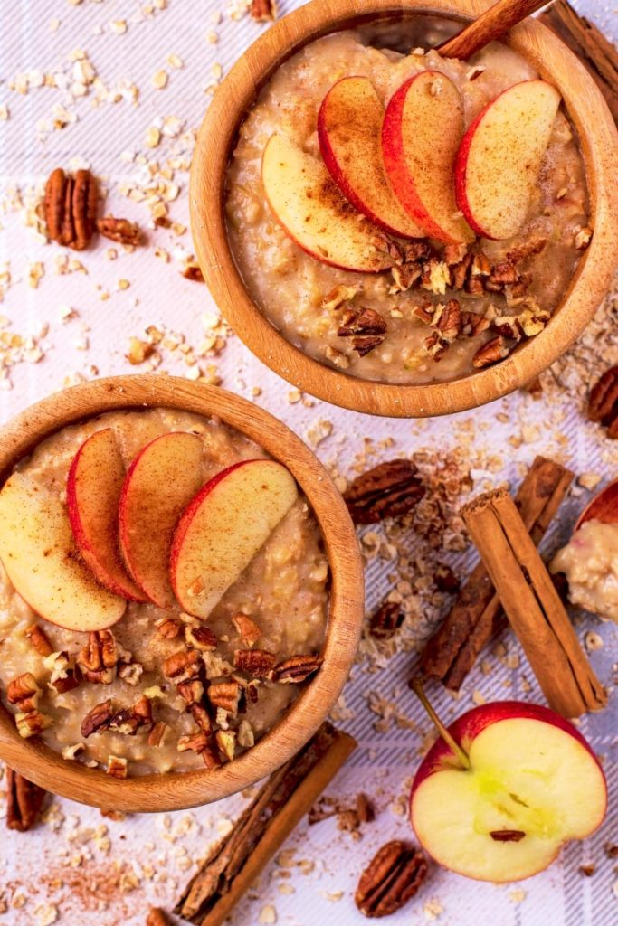 Two wooden bowls full of Apple Pie Oatmeal with sliced apple on top