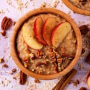 Apple Pie Oatmeal in a brown bowl with apple slices on top. Cinnamon sticks and an apple are next to it
