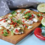 Baked Sea Bass on a serving board with red chillis and lime wedges