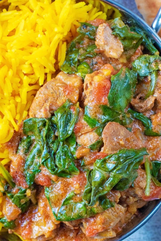 Lamb and spinach in a curry with bright yellow rice
