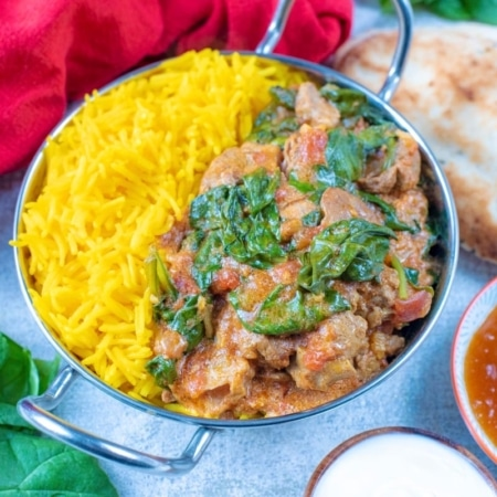 Slow Cooker Lamb Rogan Josh in a silver balti dish. Naan bread and mango chutney accompany it