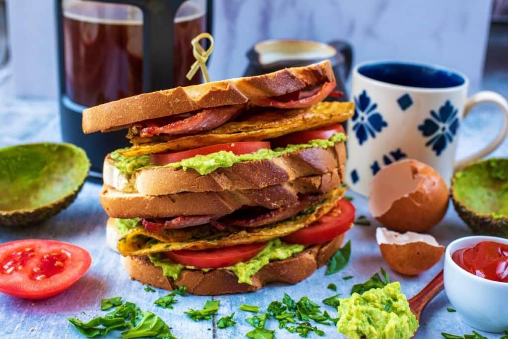 Toasted breakfast sandwich surrounded by various breakfast items