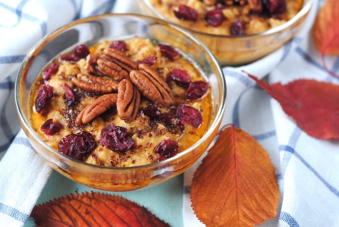 Pumpkin Porridge in a glass bowl topped wiht pecans and dried fruit