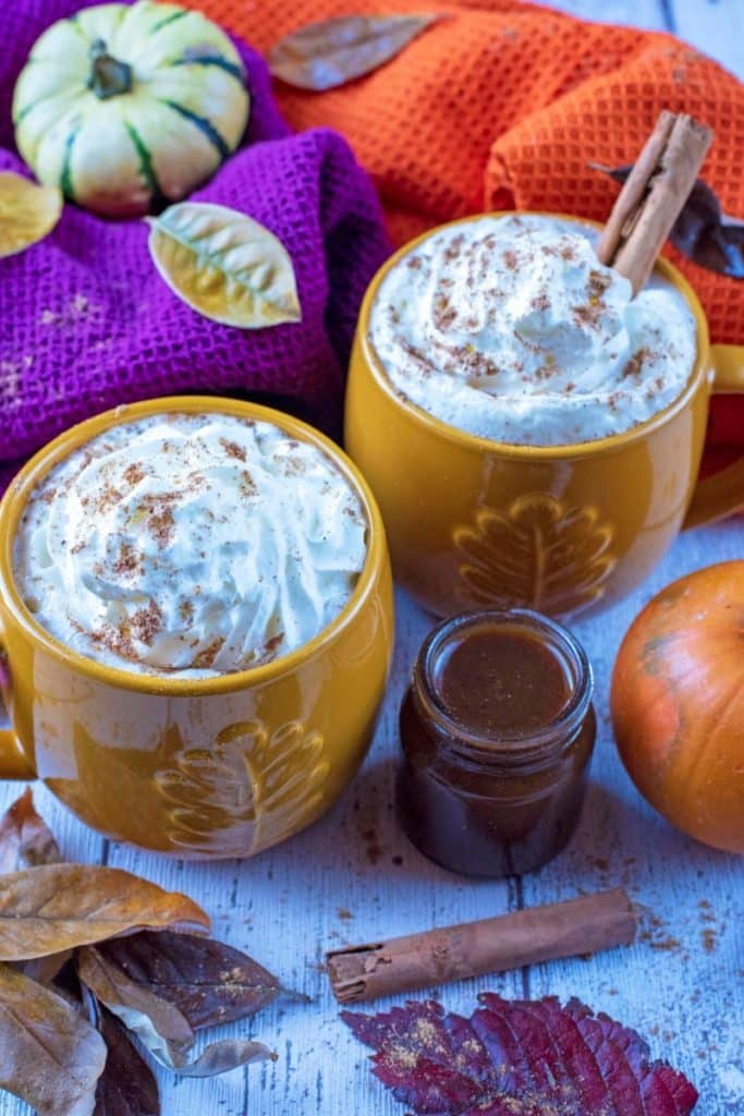 Pumpkin spice latte in an orange mug with whipped cream and a cinnamon stick