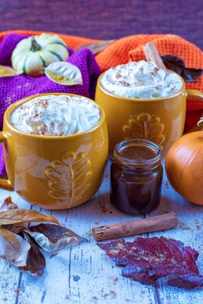 Two mugs with coffee and cream. Leaved and pumpkins surround them
